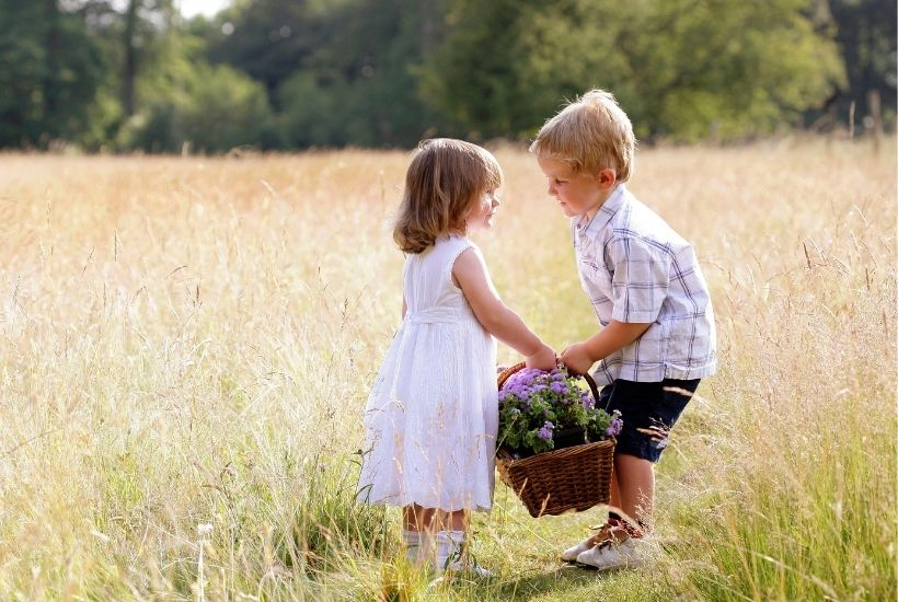 Boy helping girl carry a basket of plants in a field
